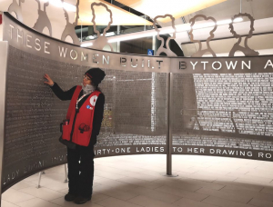 An O-Train ambassador examines the newly installed sculpture at the Lyon LRT sta- tion, which honours the 32 founders of the Women's Canadian Historical Society of Ottawa — the organization that evolved into today's Historical Society of Ottawa
